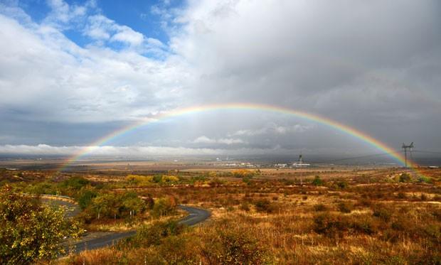 O fotógrafo Dimitar Dilkoff registrou o início e o fim de um arco-íris na mesma foto, no domingo (29), próximo a Sófia, na Bulgária. Segundo a lenda, o final do arco-íris esconderia um pote de ouro.  (Foto: Dimitar Dilkoff/AFP)