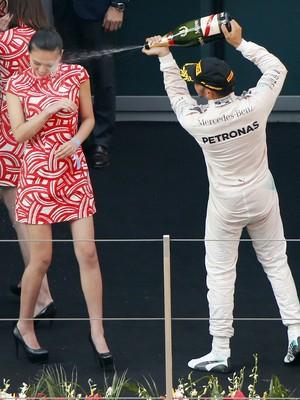 Lewis Hamilton joga champanhe em rosto de mulher no pódio do GP da China (Foto: Reuters)