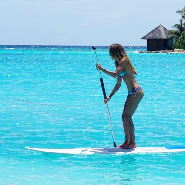 Carol Magalhães pratica stand up paddle em praia nas Maldivas (Foto: Instagram/ Reprodução)