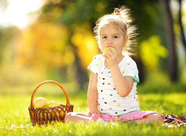 Criança comendo frutas em piquenique ao ar livre (Foto: Shutterstock)