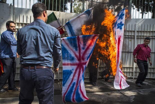 Estudantes iranianos queimam bandeiras dos EUA, Reino Unido e Israel em protesto em Teerã nesta quarta-feira (2) (Foto: Ebrahim Noroozi/AP)