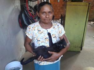 Olgarina da Luz com o único animal que cuidava que sobreviveu  (Foto: John Pacheco/G1)