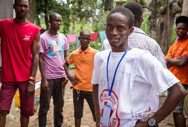 Maratonista Idrissa Kargbo participa como voluntário da distribuição de informações sobre ebola em Freetown, capital de Serra Leoa, nesta sexta-feira (19) (Foto: AP Photo/Michael Duff)