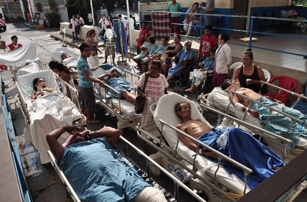 Pacientes de um hospital aguardam com familiares do lado de fora após o edifício ser esvaziado em Acapulco (Foto: Jesus Solano/Reuters)