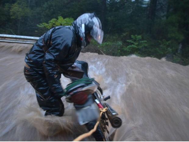 Um motoqueiro tentou ultrapassar uma enxurrada e foi salvo por um casal que passava pela rodovia  (Foto: Karin Detlinger / VC no G1)