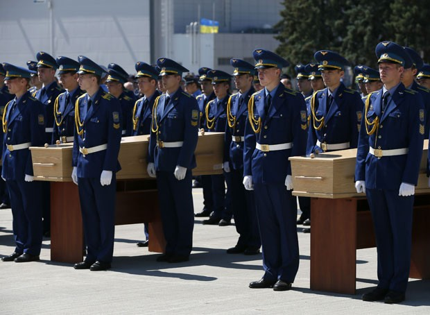 Guardas de honra participam de homenagem às vítimas do voo MH17 antes de colocarem os caixões dentro do avião militar que os levará à Holanda nesta quarta-feira (23) (Foto: Gleb Garanich/Reuters)