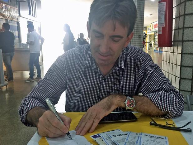 Carlos Schneider anota probabilidades sobre dezenas apostadas em uma lotérica da Asa Norte, em Brasília (Foto: Jéssica Nascimento/G1)