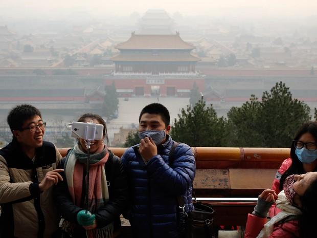 Turistas, alguns usando máscaras para se proteger da poluição, tiram uma selfie no Parque Jingshan em um dia poluído em Pequim, na China (Foto: Andy Wong/AP)