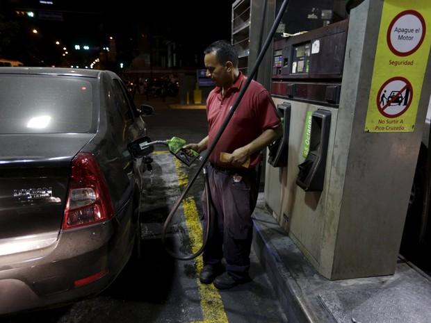 Frentista abastece veículo em posto de combustíveis de Caracas nesta quarta-feira (17). Venezuela subiu preço da gasolina após 20 anos. (Foto: Marco Bello/Reuters)