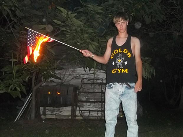 Dylan Roof queima bandeira dos Estados Unidos em foto encontrada em website racista (Foto: Reprodução/BBC)