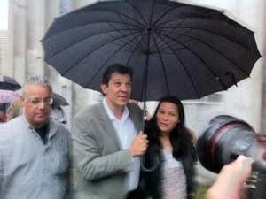 Haddad dá carona a mulher em guarda-chuva durante compromisso de campanha na Zona Leste (Foto: Rafael Sampaio/G1)