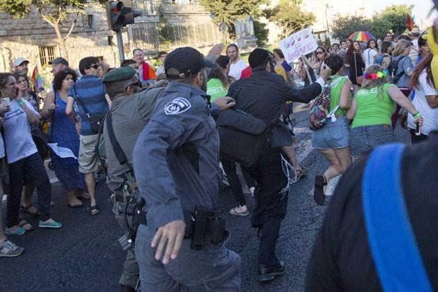 Policiais tentam conter um judeu ultraortodoxo que atacava pessoas com uma faca na Parada Gay de Jerusalém nesta quinta-feira (30) (Foto: Sebastian Scheiner/AP)