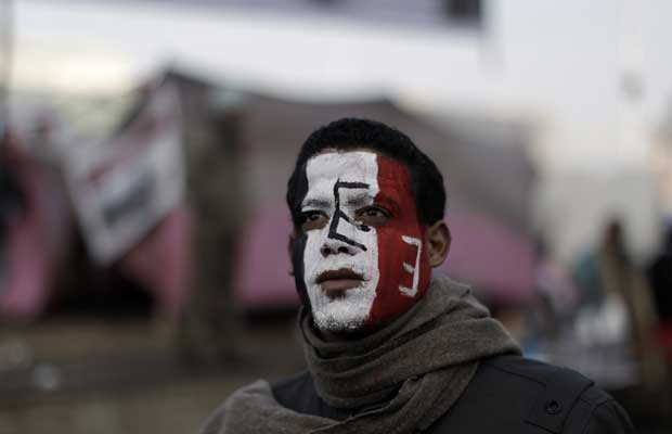Manifestante com o rosto pintado nas cores da bandeira do Egito nesta quarta-feira (25) na Praça Tahrir, no Egito (Foto: AP)