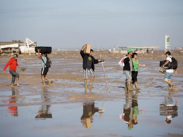 Chilenos tentam atravessar região tomada pela lama em Chanaral (Foto: Pablo Sanhueza/AP)