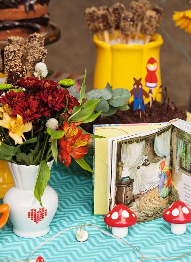 Era uma vez... Tudo começou com o livro da Chapeuzinho, em destaque na mesa do bolo repleta de flores, cogumelos de brinquedo e pirulitos de banana, banhados em chocolate e farofa de castanha-de-caju (Foto: Elisa Correa)