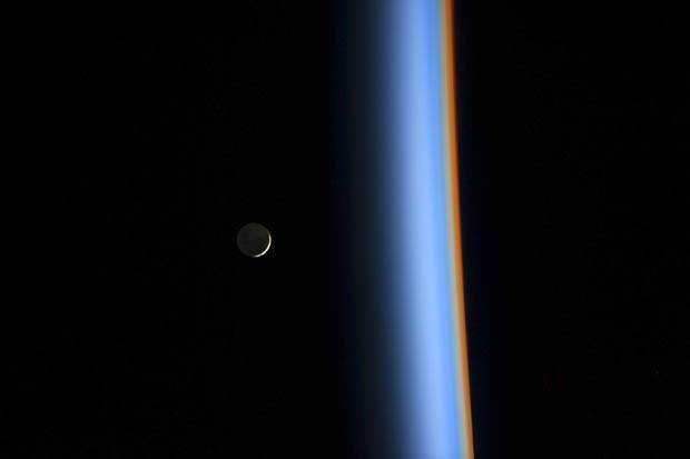Lua crescente é vista à esquerda, ao lado da luz que atravessa a atmosfera em cores diferentes à direita (Foto: Koichi Wakata/Nasa/Reuters)