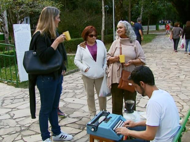 Curiosos tomam cafezinho enquanto poeta compõe em filtros em São Lourenço, MG (Foto: Reprodução EPTV)