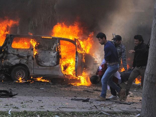 Guardas de segurança sírios carregam um corpo passando por carros em chamas no centro de Damasco, na Síria. A explosão de um carro-bomba durante a manhã perto da sede do partido Baath matou mais de 30 pessoas e feriu outras diversas, segundo ONG. (Foto: AP/Sana)