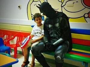 Batman e paciente conversam durante visita de heróis em Piracicaba (Foto: Antonio Trivelin/Divulgação)