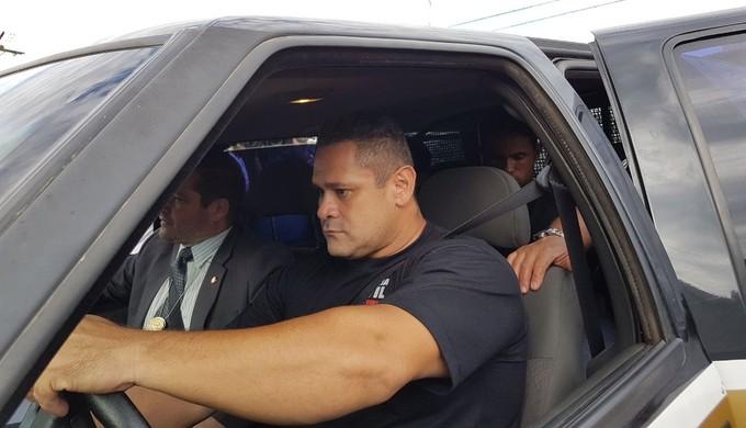 No banco de trás da viatura da polícia, Bruno chega ao presídio de Varginha (MG) (Foto: Samantha Silva)