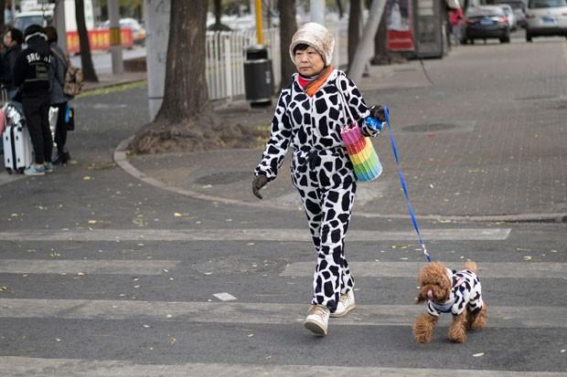 Uma chinesa e seu cão de estimação foram fotografados usando roupas combinando enquanto cruzavam uma faixa de pedestres em Pequim, capital do país, nesta terça-feira (2) (Foto: Fred Dufour/AFP)