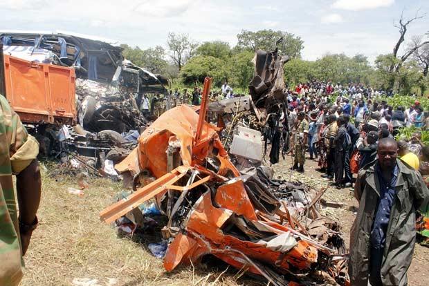 Curiosos observam destroços de ônibus e caminhão acidentados nesta quinta-feira (7) em Zâmbia (Foto: AFP)