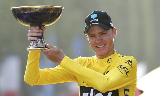 Chris Froome com o troféu de campeão do Tour de France, o terceiro dele nos últimos quatro anos. Só em 2014 o britânico não levou