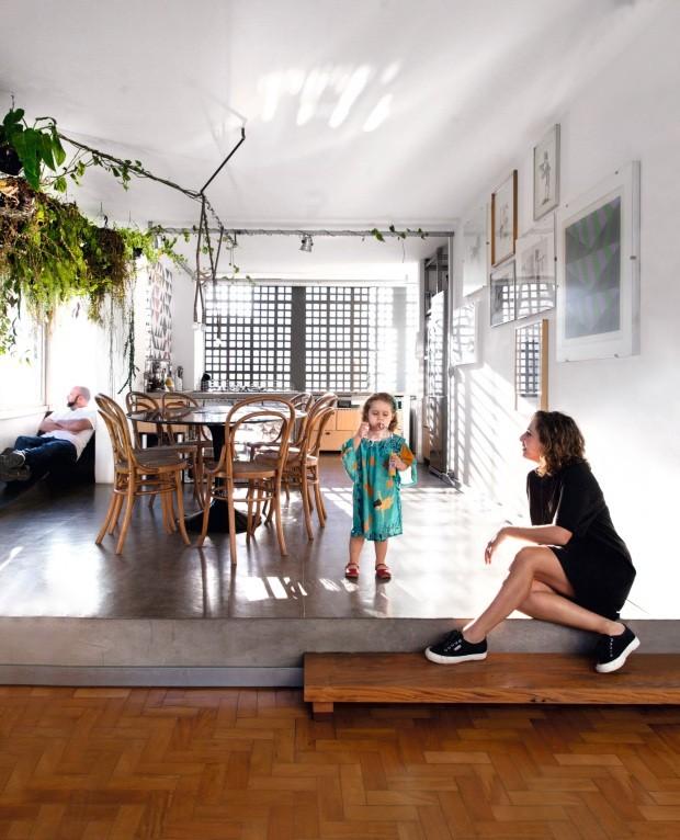 A moradora Maíra, com a filha Lina, está na sala de jantar, e seu marido, Lula, relaxa na espreguiçadeira de chapa metálica criada por ele (Foto: Maíra Acayaba / Editora Globo)