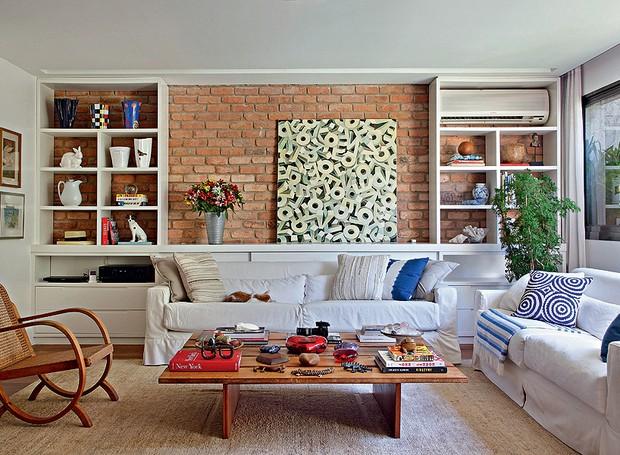 """A sala da apresentadora Patricya Travassos é aconchegante. Segundo a designer de interiores Paola Ribeiro, a ideia foi valorizar a madeira e os tijolos de demolição. """"Esses elementos remetem à sensação de casa, mesmo sendo de apartamento"""", explica (Foto: Denilson Machado/MCA Estúdio)"""
