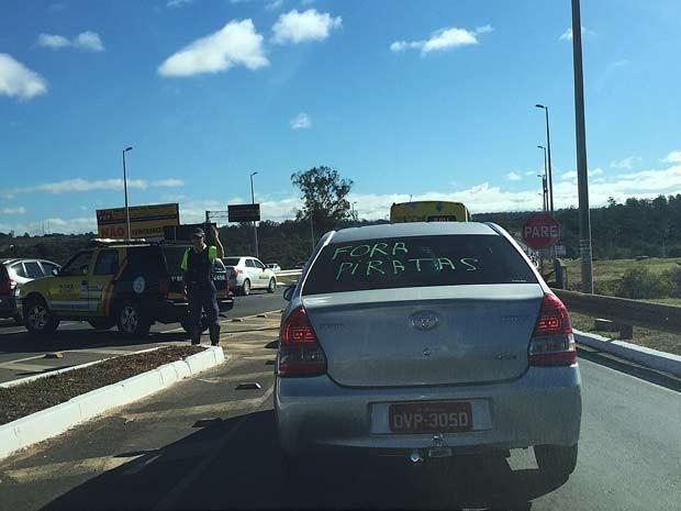 Táxi com a inscrição 'Fora piratas' durante carreata 1ue saiu do aeroporto JK em direção ao estádio Mané Garrincha (Foto: Luciana Amaral/G1)