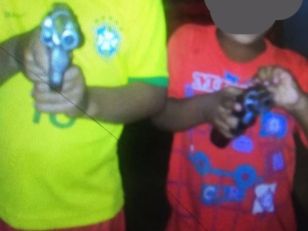 Crianças de seis e três anos de idade posam com revólveres (Foto: Denarc/Divulgação)