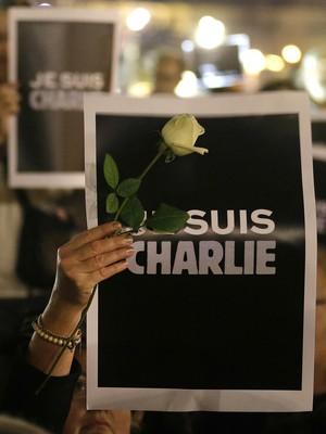 """Em Nice, no sul da França, uma mulher levanta um cartaz com os dizeres """"Je suis Charlie"""" (eu sou Charlie) em um protesto contra o ataque terrorista que matou 12 pessoas na redação do jornal satírico Charlie Hebdo (Foto: Lionel Cironneau/AP Photo)"""