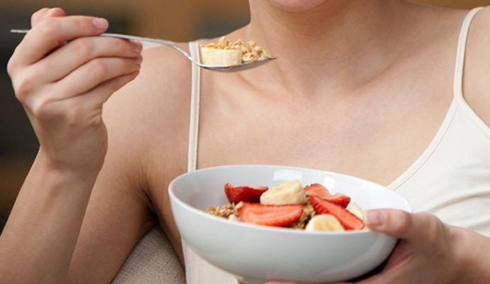 Mulher comendo salada de frutas (Foto: Getty Images)