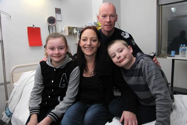 Vanessa Tanasio com seu filho Max e filha Ella, e sargento Mark Robertson da Polícia de Victoria. Ela foi trazida de volta à vida depois de ficar clinicamente morta por 42 minutos.  (Foto: AFP Photo/Philip Blackman)