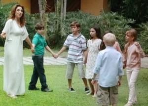 Damáris faz ciranda com crianças toda de branco (Foto: Sangue Bom / TV Globo)