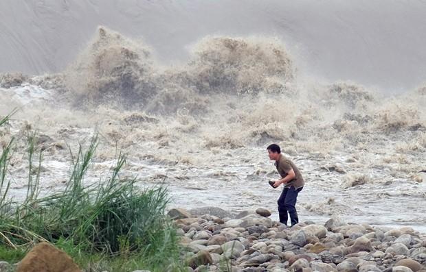 Homem pega pedras no Xindian após a passagem do tufão Dujuan, nesta terça-feira (29)  (Foto: Sam Yeh/AFP)