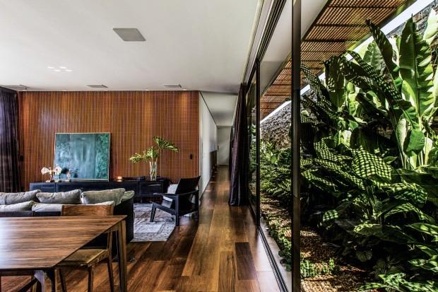 O painel de madeira ripada reveste a parede e define o módulo das quatro suítes com o corredor envidraçado para o jardim no recuo lateral (Foto: Renato Moura / Divulgação)