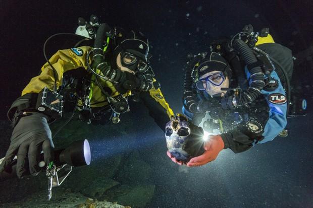Mergulhadores Alberto Nava e Susan Bird transportam o crânio para uma plataforma giratória, para que ele seja fotografado para a criação de um modelo 3D (Foto:  Cortesia de Paul Nicklen/National Geographic)