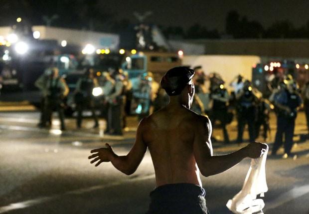 Homem é visto em frente a policiais durante protesto em Ferguson, nos EUA, nesta segunda-feira (19) (Foto: Charlie Riedel/AP)