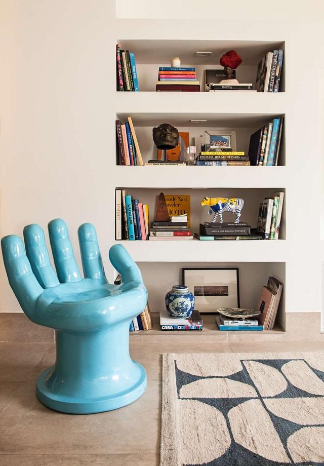 O toque de azul na sala de TV está na divertida cadeira em forma de mão e no tapete com estampa by Rem Koolhaas (Foto: Divulgação)