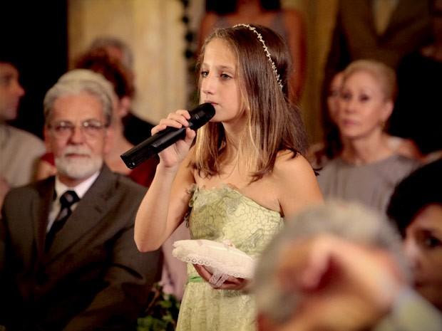 Paloma pega um microfone e diz que Cadinho é seu pai (Foto: Avenida Brasil / TV Globo)