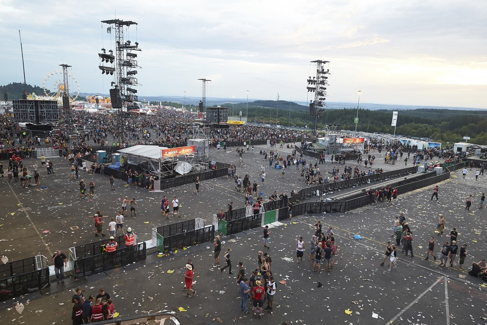 Espectadores do festival Rock am Ring, na Alemanha, deixam o local nesta sexta-feira (2) devido a uma ameaça terrorista (Foto: Thomas Frey/Dpa via AP)