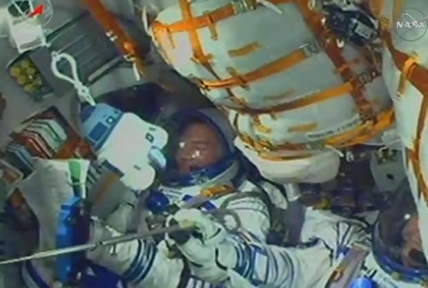 Imagem feita minutos após o lançamento do foguete Soyuz, na tarde desta quarta-feira, mostra astronautas em segurança dentro da nave. No canto esquerdo, é ´possível ver brinquedo R2D2 levado pela tripulação a bordo (Foto: Reprodução/Nasa TV)