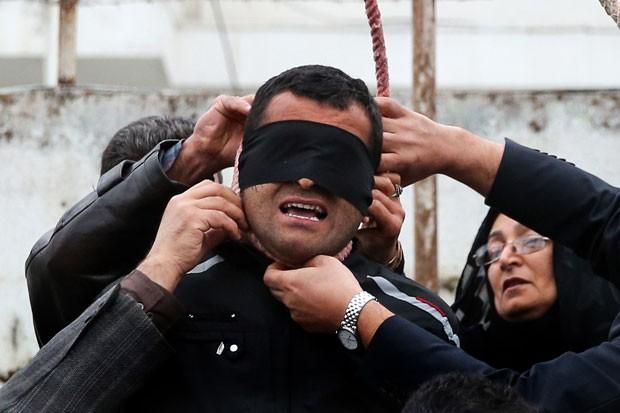 Familiares da vítima, morta há sete anos, ajudam a colocar a corda no pescoço do condenado (Foto: Arash Khamooshi/Isna/AFP)
