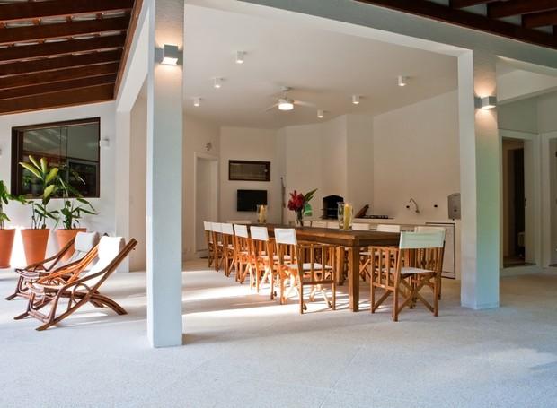 Área gourmet | A área de lazer funciona como uma extensão da casa. Com churrasqueira, forno de pizza e bancada, o espaço é perfeito para receber os amigos. Mesa e cadeiras da Casual. Piso fulget (Foto: Divulgação)