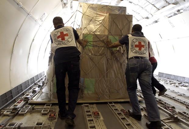 Membros do Comitê Internacional da Cruz Vermelha desembarcam mantimentos para as vítimas dos ataques no Iêmen (Foto: Mohammed Huwaus/AFP)