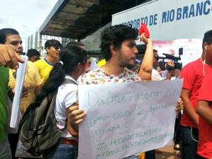 Manifestante exibe cartaz no aeroporto de Rio Branco durante chegada de Dilma (Foto: Janine Brasil/G1)