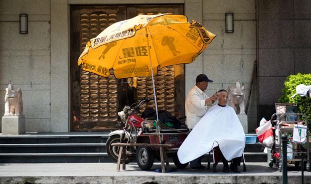 Cabeleireiro chinês montou salão móvel em Xangai (Foto: Johannes Eisele/AFP)