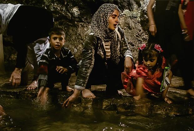 Na fonte sagrada Zamzam, no norte do Iraque, a ex-escrava sexual Turkia Hussein (centro), acompanhada de seus dois filhos, torna-se yazidi novamente (Foto: Marcio Pimenta)