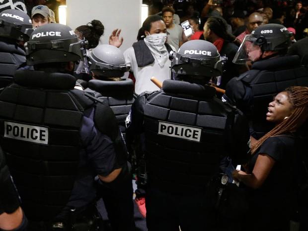 Manifestantes e policiais se enfrentam em hotel em Charlotte, na noite de quarta (21), durante protesto pela morte de Keith Lamont Scott (Foto: AP Photo/Chuck Burton)
